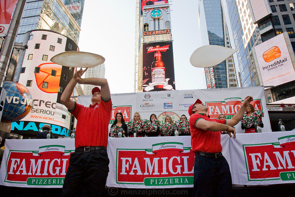 Performers entertain the audience at the  Famous Famiglia world championship pizza eating contest in New York City's Times Square before the eating contest by throwing pizza dough in the air. Joey Chestnut won the competition by eating 45 slices of cheese pizza in 10 minutes. Each slice weighed 109 grams (3.84 ounces) and contained 260 calories. In ten minutes Joey consumed 10.81 pounds (4.9 kilograms) of pizza and drank a gallon of water. The pizza contained 11,700 calories.