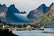 Fog from the Norwegian Sea (part of the North Atlantic Ocean) flows over mountains towards the fishing village of Reine on Moskenesøya (the Moskenes Island), in the Lofoten archipelago, Nordland county, Norway.