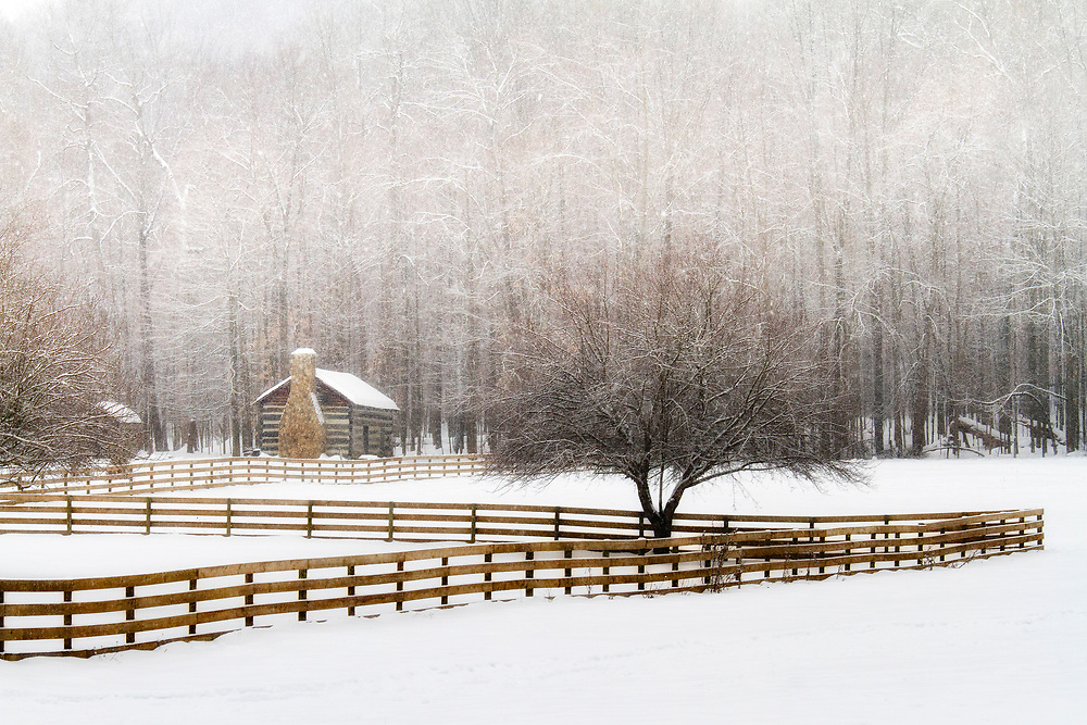 A quaint log cabin and long fence are a nice compliment to the beautiful trees, heavy with snow.<br />