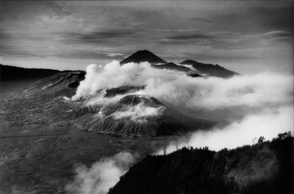 Bromo volcano (center left) emits a plume of steam in a massive flat crater it shares with several dormant cones, including Batok (center) and the perfect cone of Gunung Semeru looms in the distance, Java's highest peak and one of the most active volcanoes on the island.  Indonesia.