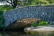 Old stone bridge over Esk River. Eskdale Trail, in Lake District National Park. England Coast to Coast hike with Wilderness Travel, day 2 of 14: from Eskdale in Cumbria county, we walked to Boot for lunch at a local pub and a visit to a working medieval corn mill, in the United Kingdom, Europe. We then climbed to Burnmoor Tarn, then descended to the hamlet of Wasdale Head. Via minibus we returned to Irton Hall for the second night. [This image, commissioned by Wilderness Travel, is not available to any other agency providing group travel in the UK, but may otherwise be licensable from Tom Dempsey – please inquire at PhotoSeek.com.]