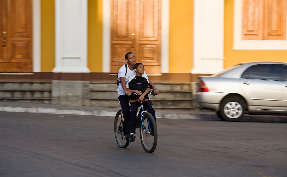 Two boys on the same bicycle bike to school in Grenada. Grenada is located on the shores of Lake Nicaragua. It is a classic Spanish colonial city that is more than 350 years old and was once burned down by the North American filibuster William Walker.