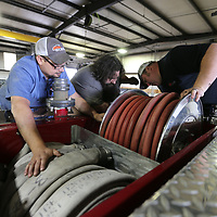Thomas Wells | BUY at PHOTOS.DJOURNAL.COM<br /> Chris Hutcheson, from left, David Yarabrough and Jason Bridges look at replacing the automatic rewind motor for a fire hose on a reserve firetruck at the Tupelo Public Works repair shop.