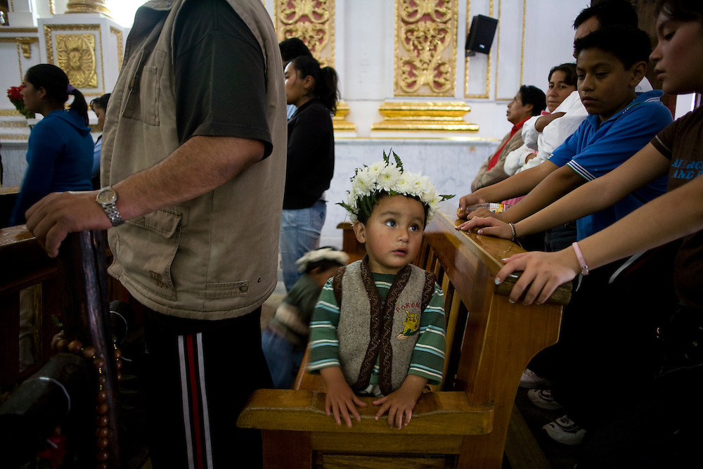 A young boy wearing a crown of flowers sits during mass at the church in Chalma.  Chalma is the second most important pilgrimage site in Mexico.  People come from all over the country to visit the Senor de Chalma. They often arrive wearing crowns made of flowers, and leave the crowns at the church.