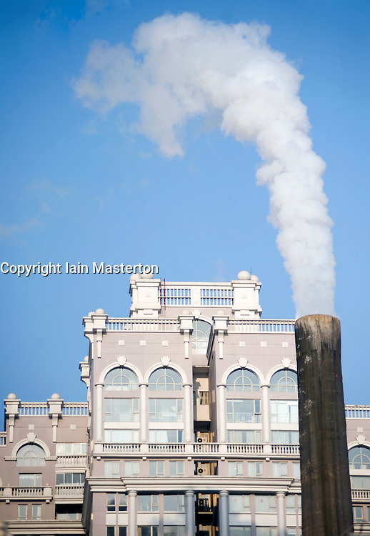Smoke emissions from an old coal fired power station close to new high rise apartment building in central Beijing China