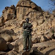 A SPLA-North fighter takes guard near some temporary shelters in caves outside Buram village in South Kordofan's Nuba Mountains.