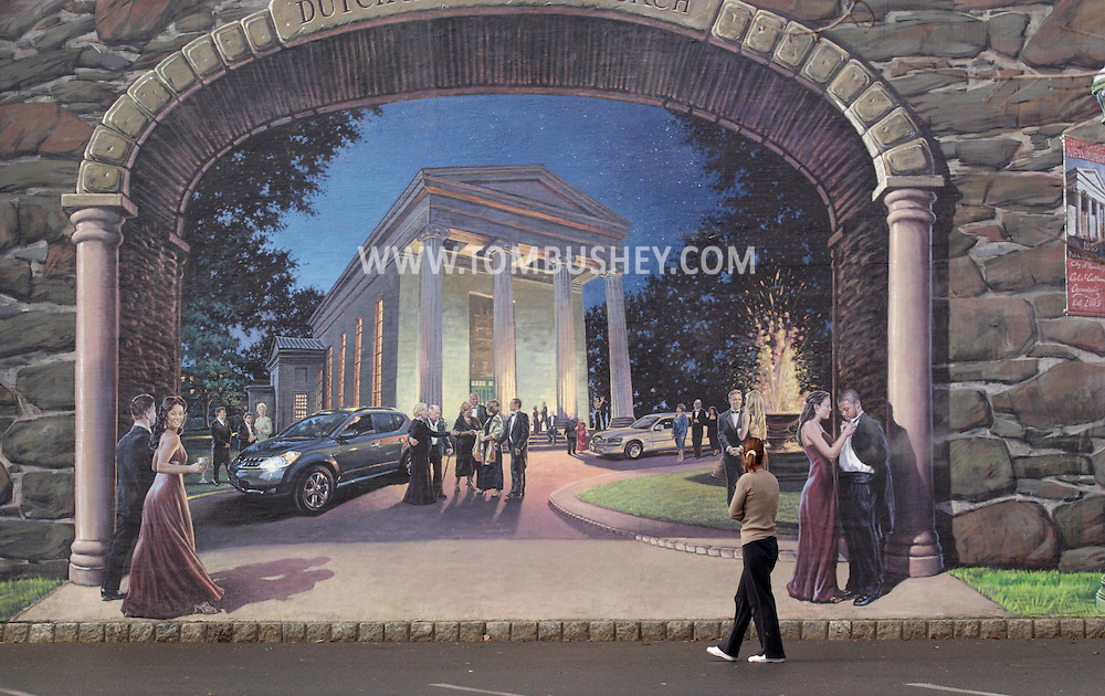 """Newburgh, NY - A woman looks at the """"Arches of Newburgh"""" mural painted on teh CSX Railroad trestle on the Newburgh waterfront on Feb. 5, 2008. The 220-foot long mural was painted by Garin Baker. The building in this part of the mural is the Dutch Reformed Church."""