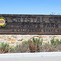 Photo of Crystal Cove State Park sign. Crystal Cove is a popular attraction known for its rock formations, tide pools, and scenic beach. Crystal Cove State Park is located along the Pacific Ocean in Laguna Beach in Orange County Southern California.