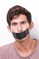 Portrait of young man with tape over his mouth staring over white background