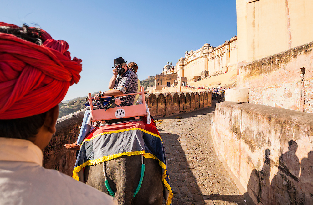 A view from atop an elephant looking at the back of the elephant drivers head and other tourists as they go up the ramps to Amer Palace, Amer, Rajasthan, India.