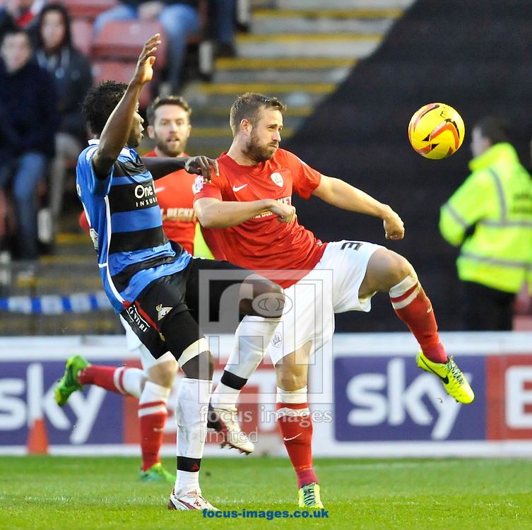 Picture by Richard Land/Focus Images Ltd +44 7713 507003<br /> 09/11/2013<br /> David Fox of Barnsley clears under pressure from Bongani Khumalo of Doncaster Rovers during the Sky Bet Championship match at Oakwell, Barnsley.