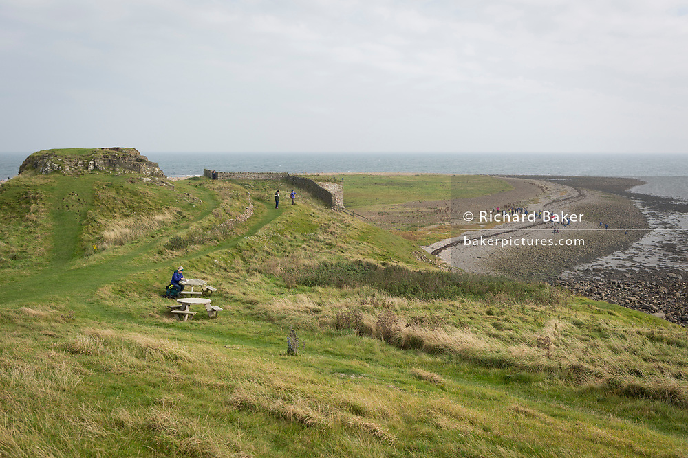 A visitor to Holy Island sits on a picnic table to read a book at a location overlooking Victorian lime kiln ruins and the North Sea, on 27th September 2017, on Lindisfarne Island, Northumberland, England. The Holy Island of Lindisfarne, also known simply as Holy Island, is an island off the northeast coast of England. Holy Island has a recorded history from the 6th century AD; it was an important centre of Celtic and Anglo-saxon Christianity. After the Viking invasions and the Norman conquest of England, a priory was reestablished.