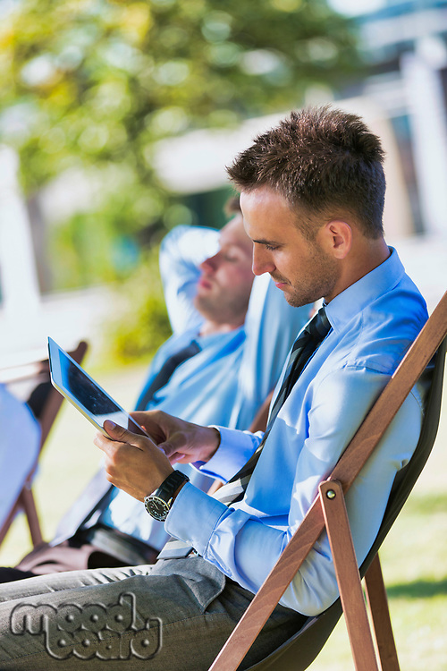 Handsome businessman sitting on folding chair in park while using digital tablet