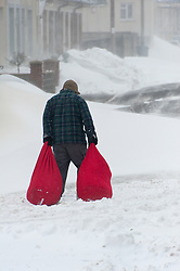 © Licensed to London News Pictures. 2/03/2018. Brynmawr, Blaenau Gwent,, South Wales, UK. Workers brave the relentless storm to carry laundry for a local nursing home to be cleaned. People battlle against the blizzard, snowdrifts and horrendous weather conditions as Storm Emma continues without mercy at Brynmawr in South Wales (the highest town in Wales.)  Photo credit: Graham M. Lawrence/LNP