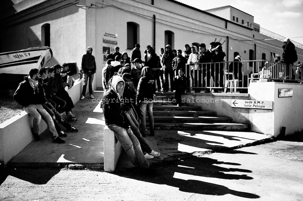 ITALY, Lampedusa : Immigrants who arrived on the island of Lampedusa in the last days relax on the stairs of a building in the center of Lampedusa on February 15, 2011. Over 2,000 Tunisians asylum-seekers who have arrived on the island following the North African country's popular uprising are now being lodged in a reopened reception centre. AFP PHOTO / ROBERTO SALOMONE