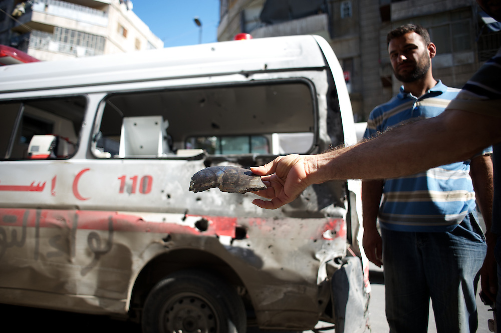 August 14, 2012 - Aleppo, Syria: Medical staff shows shrapnel from the bomb shot at their ambulance in Tariq Al-Bab neighborhood in central Aleppo. The Syrian Army have in the past ten days increased their attacks on residential neighborhoods where Free Syria Army rebel fights have their positions in Syria's commercial capital, Aleppo. (Paulo Nunes dos Santos/Polaris)