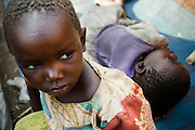 A girl sits on a floor mat while her sister lies down at the Kiwanja MONUC IDP camp in near the town of Kiwanja, Eastern Democratic Republic of Congo, during a visit on Thursday December 11, 2008. Nearly 5,000 people have set camp outside the UN base here, seeking protection, after recent violence forced them to flee their homes.