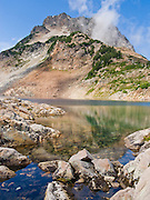 Del Campo Peak rises above Foggy Lake in Gothic Basin, in the Cascade Mountains of Washington, USA. Hike 10 miles round trip with 3300 feet gain along a mostly steep and rough trail, starting from the trailhead at Barlow Pass on the Mountain Loop Highway, 20 miles east of Verlot Visitor Center, in Mount Baker - Snoqualmie National Forest.