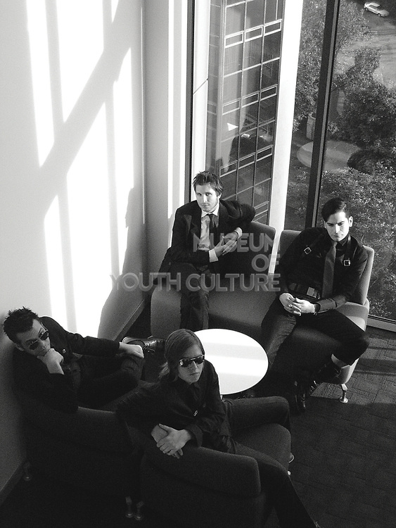 Four young stylish men casually sitting and looking up.