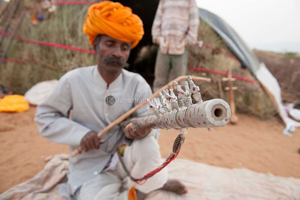 A man playing a ravanatha instrument in the desert, Pushkar, India.