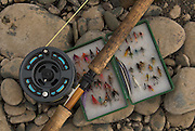 Riverbak still life showing flyfishign rod, reel and tackle, flies.