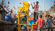 Man grinding ice at dock before going fishing in Diu (India)