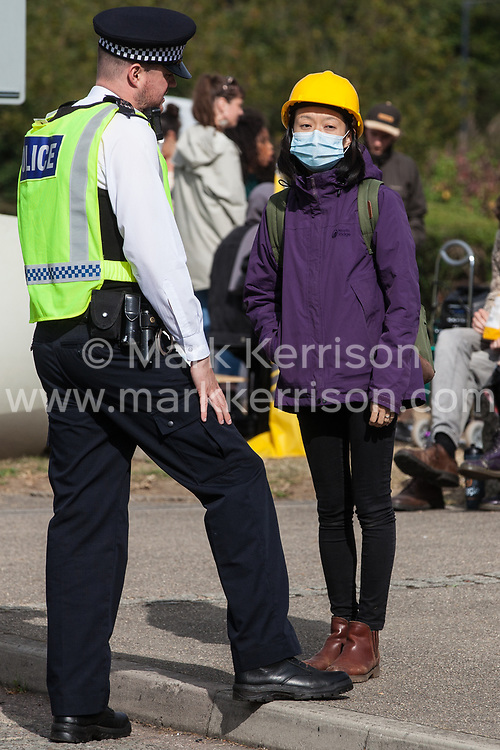 London, UK. 7 September, 2019. An activist wearing a mask and yellow helmet in solidarity with pro-democracy campaigners in Hong Kong speaks to a Metropolitan Police officer on the sixth day of Stop The Arms Fair protests outside ExCel London against DSEI, the world's largest arms fair. The sixth day of protests was billed as a Festival of Resistance and included performances, entertainment for children and workshops as well as activities intended to disrupt deliveries to ExCel London for the arms fair.
