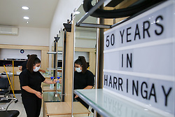 © Licensed to London News Pictures. 30/06/2020. London, UK. A member of staff in Cheriee on Green Lanes in Harringay, north London, cleans the mirror as Cheriee prepares to reopen on 4 July. Hairdressers across the UK closed on 23 March following the coronavirus lockdown. As coronavirus lockdown restrictions are eased, hairdressers will reopen on Saturday 4 July. Photo credit: Dinendra Haria/LNP