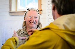 Joanne Waterman (left) speaks with Haines resident Mike Erny during  a recent open house celebrating the completion of the restoration of the fire hall on the grounds of historic Fort William H. Seward in Haines, Alaska.<br /> <br /> The fire hall was restored over a two-year period by owners Waterman and Phyllis Sage who also own the fort&rsquo;s original guardhouse, now a bed and breakfast, located next door to the fire hall.<br /> <br /> After being absent from the historic Fort Seward skyline since approximately the 1930s, the 60-foot tower of the fort&rsquo;s fire hall has been restored to its original height. The building and tower, built around 1904 in Haines, Alaska, was shortened to approximately half its height in the 1930s for unknown reasons. The restoration included rebuilding a missing 35-foot section of the 60-foot tower whose purpose was to dry fire hoses. The tower restoration was completed by building its four sections on the ground and then hoisting those sections with a crane into place on top of each other.<br /> <br /> Through the years, the historic Fort Seward area, a former U.S. Army post, has been referred to as Fort William H. Seward, Chilkoot Barracks, and Port Chilkoot. The National Historic Landmarks listing record for the fort says that &quot;Fort Seward was the last of 11 military posts established in Alaska during the territory's gold rushes between 1897 and 1904. Founded for the purpose of preserving law and order among the gold seekers, the fort also provided a U.S. military presence in Alaska during boundary disputes with Canada. The only active military post in Alaska between 1925 and 1940, the fort was closed at the end of World War II.&rdquo; <br /> <br /> The bottom portion of the fire hall is being leased as commercial space. Due to fire code restrictions there is no public access to the upper portion of the tower.