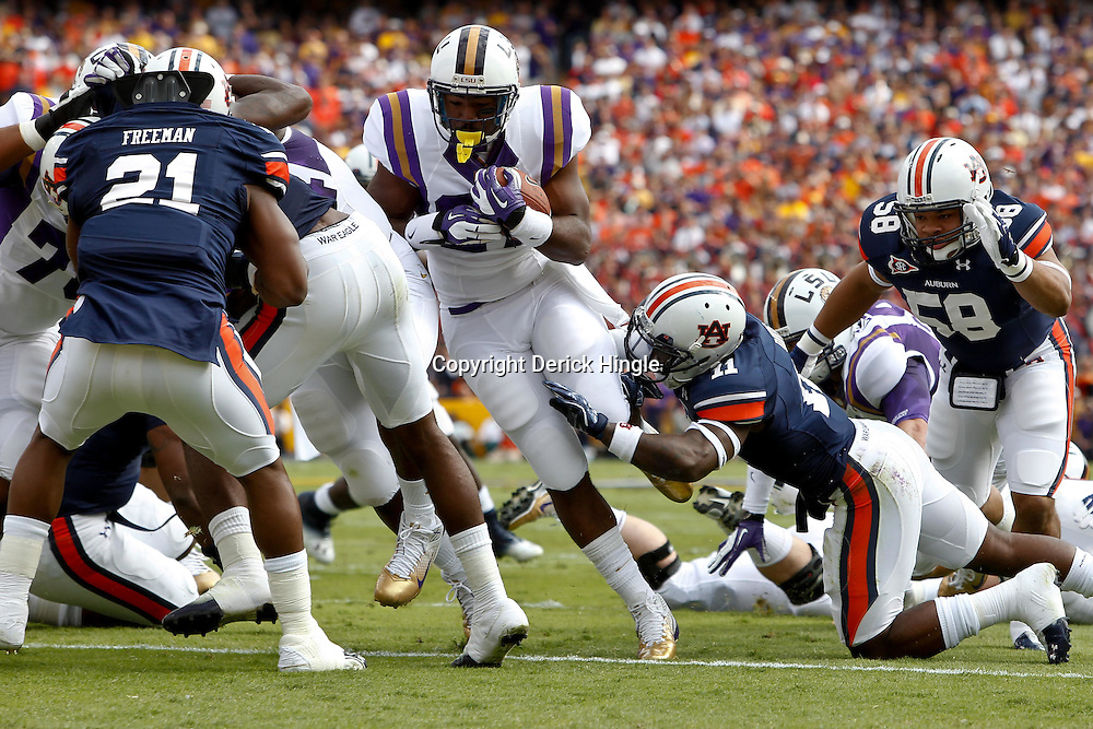 October 22, 2011; Baton Rouge, LA, USA; LSU Tigers running back Kenny Hilliard (27) runs for a touchdown against the Auburn Tigers during the first quarter at Tiger Stadium.  Mandatory Credit: Derick E. Hingle-US PRESSWIRE / © Derick E. Hingle 2011