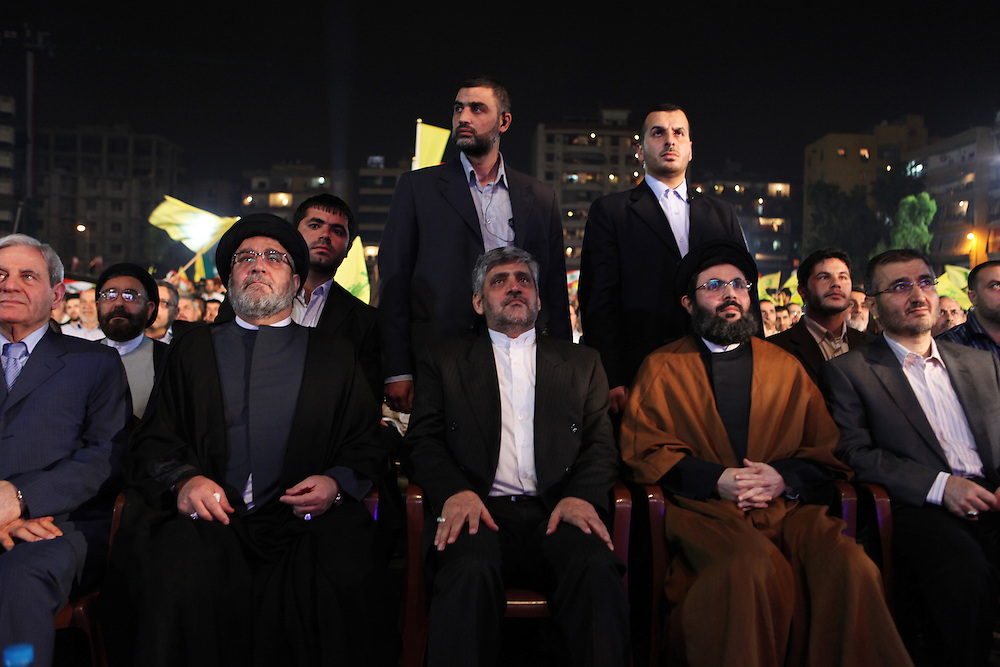 Supporters of the Shiite resistance and political group, Hizballah, rallied in the Dahiyeh southern suburbs of Beirut to watch a televised speech from Hizballah General Secretary Hassan Nasrallah. The rally was called for by Hizballah to celebrate Land Day, which is the 9th anniversary of Israel's withdrawal from southern Lebanon, which Hizballah and its supporters say was a victory over Israel. The rally comes just 13 days before Lebanese go to the polls to elect a new parliament. With Sunni Muslims and Shia Muslims mostly supporting their respective sectarian parties, Nasrallah praised Christian leader Michel Aoun. Aoun is head of the Free Patriotic Movement, which is allied with the Hizballah-led opposition March 8 coalition.///The Iranian ambassador to Lebanon (center) listens to the speech of Hassan Nasrallah.