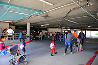 Food recipients enter a shaded parking garage to pick up basics from a La Paz Park distribution point. The site is managed by Celebration Worship and supplied by the Food Bank of Monterey County.