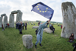 © Licensed to London News Pictures.21/06/2016. Stonehenge, Amesbury, Wiltshire, UK. A woman waves an EU flag at the Summer Solstice celebrations at Stonehenge, just before the EU referendum. This year is a leap year and so the actual Solstice fell on 20 June. There was also a 'Strawberry' full moon to coincide with the Solstice, the first time for decades. Photo credit : Simon Chapman/LNP