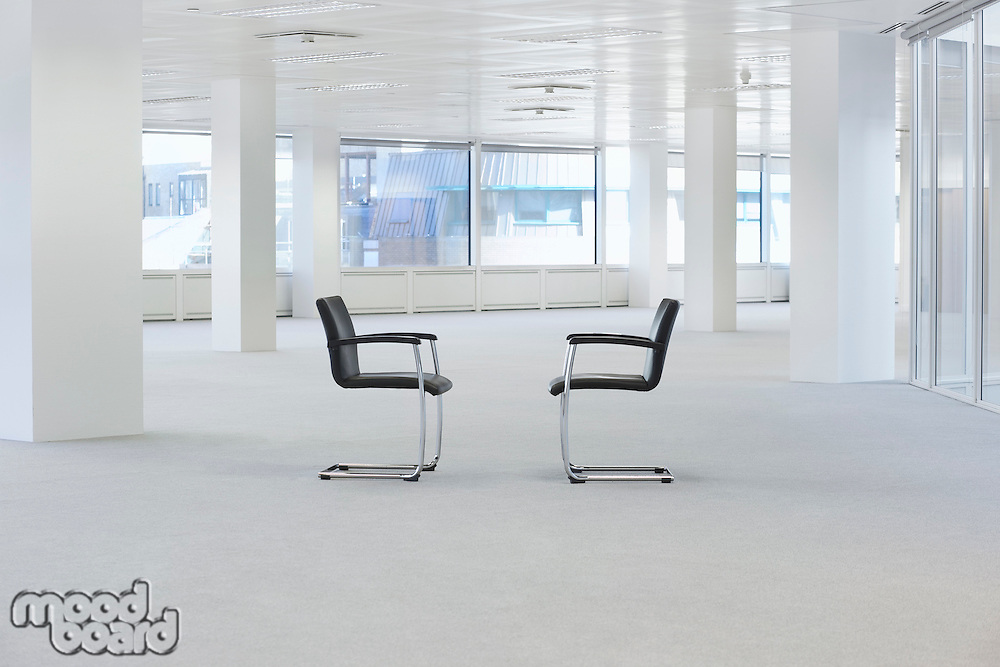 Two facing chairs in empty office space
