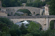 The early school bus crosses one of the bridges at the pretty French medieval walled village of Lagrasse on the River Orbieu, on 23rd May, 2017, in Lagrasse, Languedoc-Rousillon, south of France. Lagrasse is listed as one of France's most beautiful villages and lies on the famous Route 20 wine route in the Basses-Corbieres region dating to the 13th century.