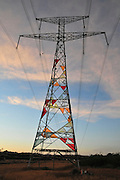 Israel, Negev Desert. High voltage power line pylon at sunset