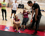 Alex Caldwell, sitting at left, laughs with teammates at track practice at St. John Fisher College on Friday, November 7, 2014.