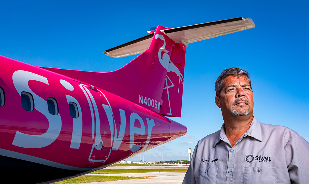 A Silver Airways maintenance supervisor stands before their newest aircraft, an ATR 42-500, at their facility in Orlando, Florida.