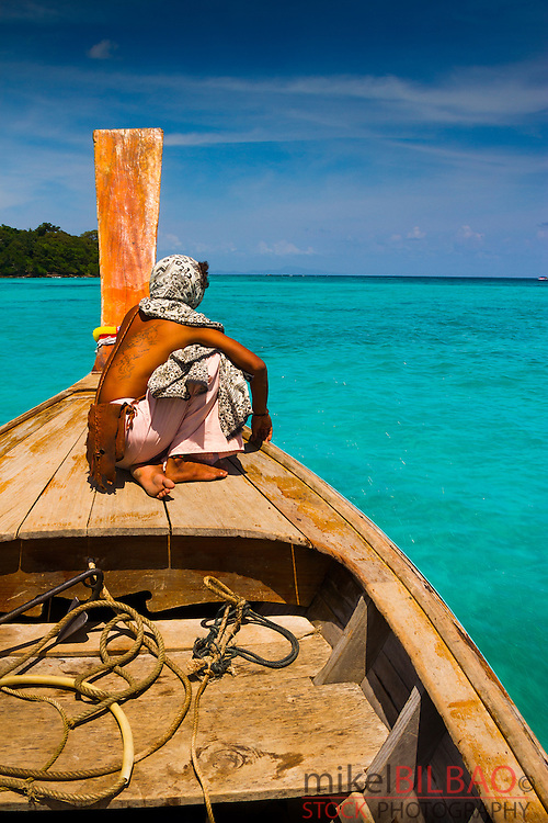 Native men in a longtail boat on Long beach. Phi Phi Don island. Krabi province, Andaman Sea, Thailand.
