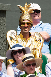 © Licensed to London News Pictures. 09/07/2018. London, UK. Spectator sitting on the centre court dressed as a golden trophy  during the Wimbledon Tennis Championships 2018, at the All England Lawn Tennis and Croquet Club. Photo credit: Ray Tang/LNP