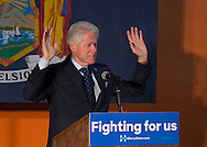 Elmont, New York, USA. April 5, 2016. Former President Bill Clinton, raising his hands up as if to say stop while giving a speech, is the headline speaker as he campaigns at an Organizing Event rally in Elmont, Long Island, on behalf of his wife, Hillary Clinton, the leading Democratic presidential candidate, and former Secretary of State and U.S. Senator for New York. Podium has 'Fighting for us' slogan on sign. The New York Democratic Primary takes place April 19th.