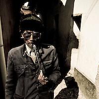Man smoking pipe in alley, Lijiang, China