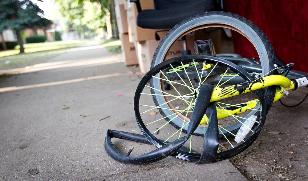MILWAUKEE, WI — AUGUST 8, 2014: A broken children's bike sits on the sidewalk outside 4350 88th Avenue on the North Side of Milwaukee during a tenant eviction.