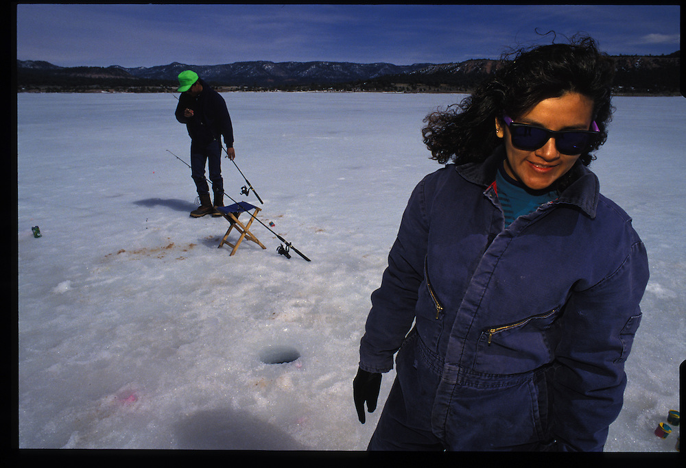 Showcasing the reservation's spectacular scenery, alpine highlands rise above the Wheatfield Lakes near Tsaile.  Ice fishing are Ramona and Calvin Cargo (Granado).