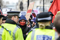 A masked anti-fascist protester confonts a police cordon at a Pegida(Patriotic Europeans Against the Islamisation of the West) rally in Whitehall, London. Feb 2016