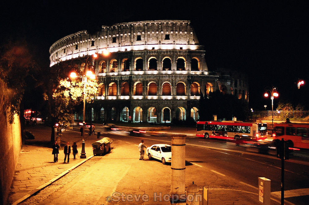 The Colosseum in Rome Italy at night is still a hub of activity with city buses, a major street and bus stop in addition to the tourists from all over the world who come to admire this ancient work, November 2005.