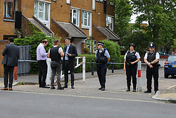 © Licensed to London News Pictures. 04/07/2020. London, UK. Detectives and police officers near a cordoned area on Roman Way, Islington in north London as police launch a murder investigation following fatal shooting. Police were called at at 3.20pm to Roman Way, following reports of shots fired.  Officers attended with LAS and found a man, believed to be aged in his early 20s, suffering from gunshot injuries. Despite their best efforts, he was pronounced dead at the scene. Photo credit: Dinendra Haria/LNP