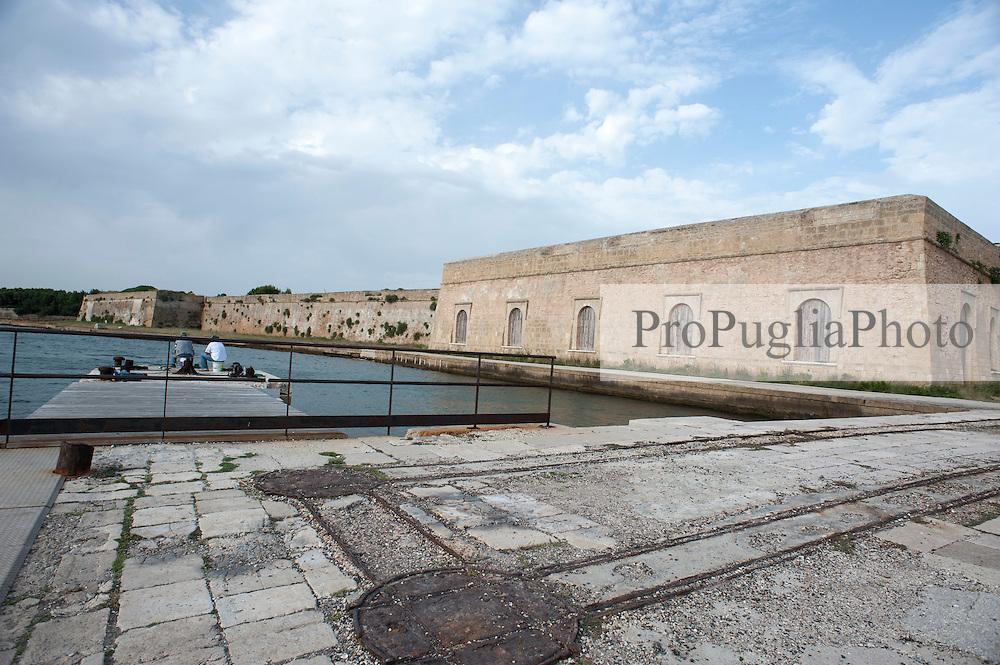 Brindisi, Castello (Alfonsino) Aragonese.<br /> Il castello alfonsino (detto anche Castel Rosso dal colore dei conci di carparo usati per la sua costruzione, o castello di Mare) &egrave; una complessa opera fortificata costruita sull'isola di Sant'Andrea, all'imboccatura del porto esterno di Brindisi. Il castello &egrave; contiguo al Forte a mare, i cui lavori di costruzione, iniziati nel 1558, regnante Filippo II d'Austria, figlio di Carlo V, durarono ben 46 anni.<br /> <br /> Il castello alfonsino occupa il promontorio meridionale con forme irregolari che seguono la conformazione del luogo (ha subito anche crolli e ricostruzioni): all'interno &egrave; un salone decorato da un lavabo con stipiti in pietra (XVI secolo). Alla fine del XV secolo risalgono i due baluardi, rotondo quello verso l'interno, triangolare quello verso il mare aperto.<br /> Caratteristico &egrave; il suo piccolo porto interno, cui si accede per un archivolto aperto nelle mura che verso il 1577 congiunsero le costruzione aragonese all'ampliamento spagnolo. Da una parte la struttura fortificata quattrocentesca con un portale; dall'altra la cosiddetta Opera a corno che segue i dettami dell'architettura fortificata cinquecentesca. Anche questa parte &egrave; preceduta da un portale adorno di stemmi.<br /> L'isola &egrave; saldata alla sponda ovest da una diga che chiude la Bocca di Puglia, mentre tra l'isola e la sponda sud si protendono due dighe che restringono l'imboccatura del porto a 250 metri.<br /> <br /> L'isola era occupata almeno dal XI secolo dall'antica abbazia benedettina di Sant'Andrea all'Isola (pochissimi i resti, in particolare capitelli, visibili al Museo archeologico provinciale Francesco Ribezzo di Brindisi), che per&ograve; fu abbandonata dopo gli eventi che sconvolsero la citt&agrave; (XIV-XV secolo). Alfonso V d'Aragona nel 1445 decise cos&igrave; di costruire una prima torre, sorta come avamposto difensivo del porto all'estremit&agrave; dell'isola; l'opera venne poi prolung