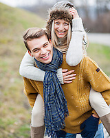 Portrait of happy man piggybacking woman in park