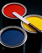 3 colorful cans of screen printer's ink are arranged on dark background with a metal palette knife on top.